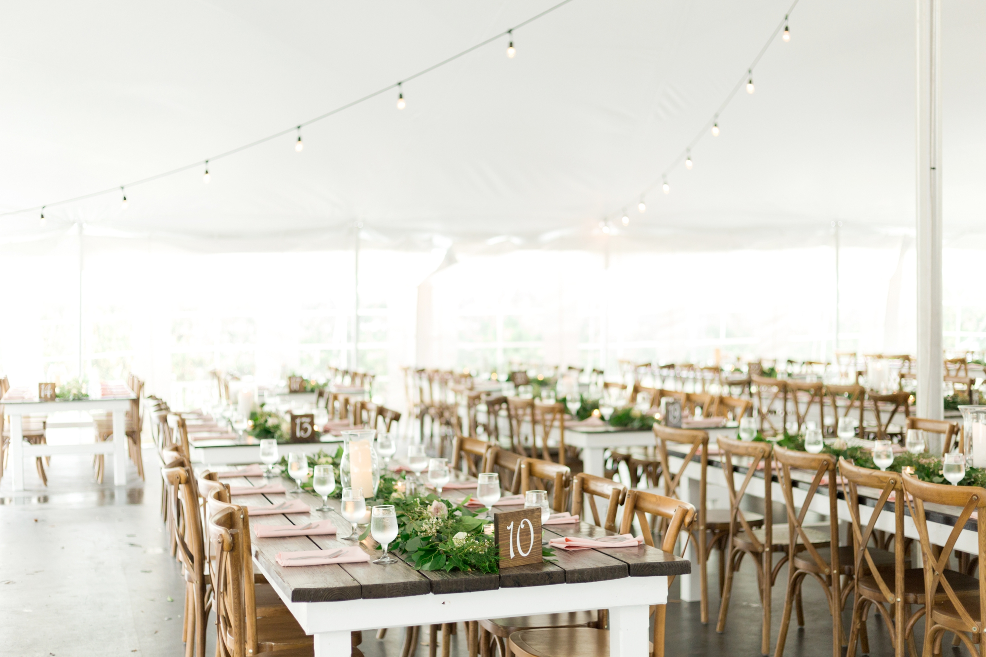 wooden tables at tented reception